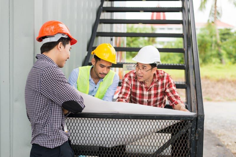 Kläderhjälmen för tre tekniker sitter på en trappuppgång och ser ett konstruktionsplan eller gör en skiss av i vitbok fotografering för bildbyråer