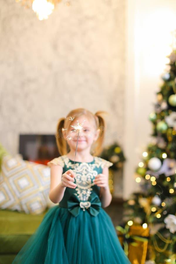 Klänningen och anseendet för liten kvinnlig unge near den bärande med bengal ljus julgranen royaltyfri bild