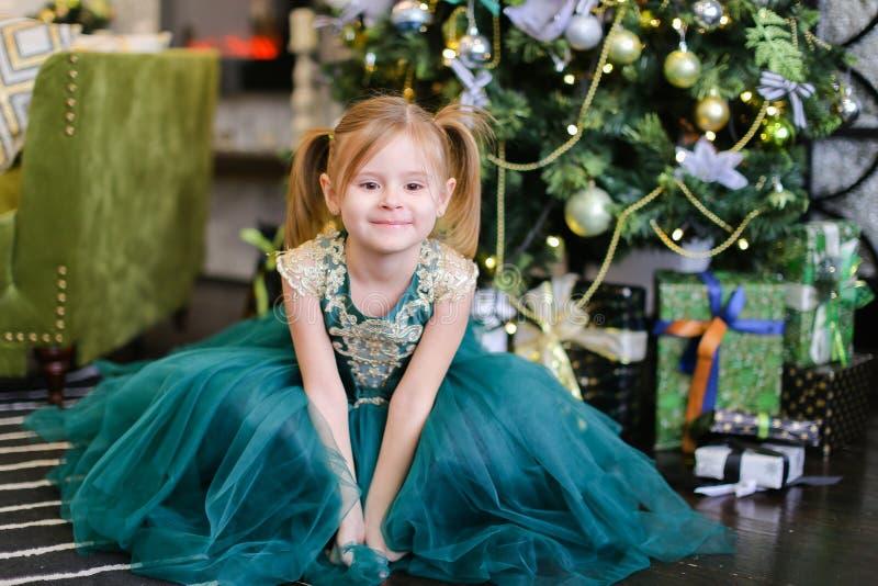 Klär bärande blått för liten härlig flicka den stående near julgranen royaltyfri fotografi