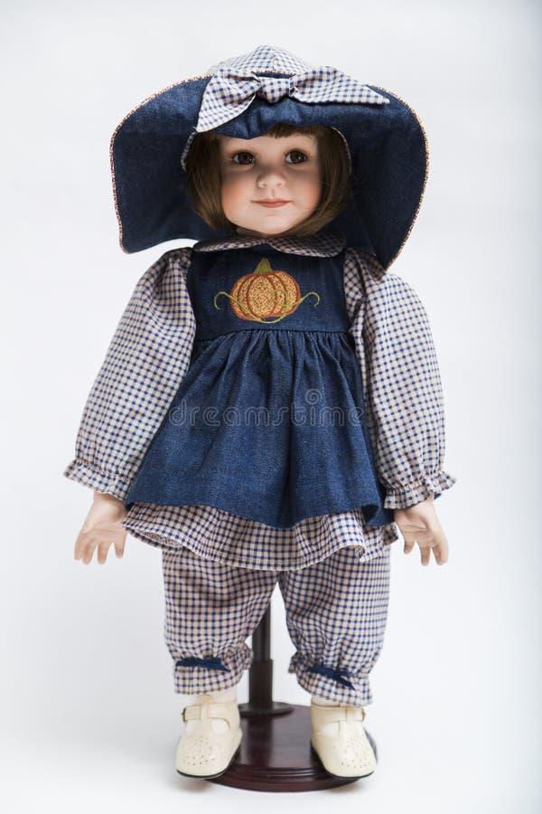 Klär den handgjorda brunettdockan för keramiskt porslin i stor hatt och blått royaltyfria foton