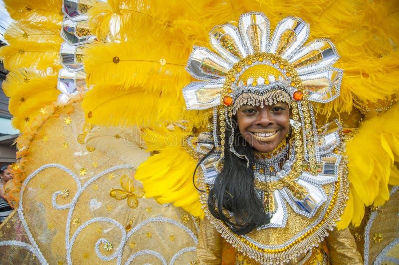Klätt i en ljus guling- och guldmaskerad tycker om en ung le kvinna karnevalet för barn` s ståtar i St James Trinidad arkivfoton
