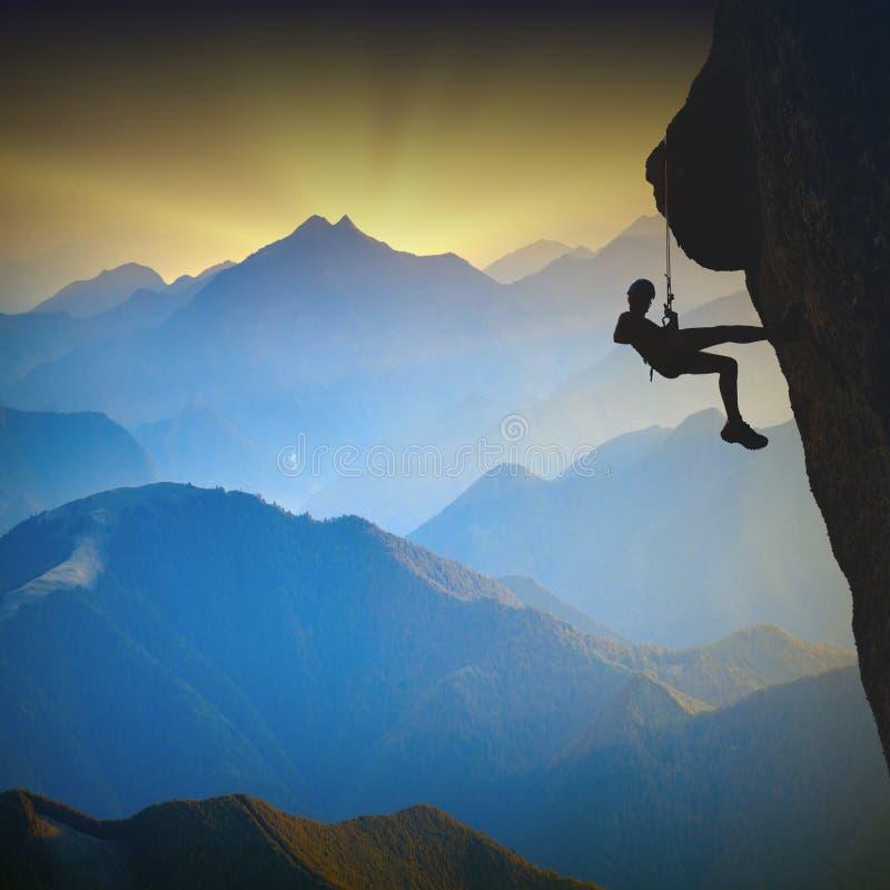 Klättrare på en klippa mot dimmiga berg royaltyfria bilder