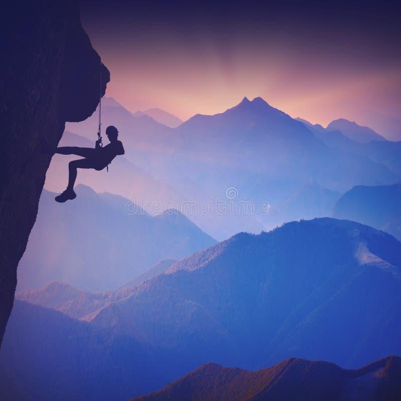 Klättrare på en klippa mot dimmiga berg - och Spedition fotosamling arkivfoton