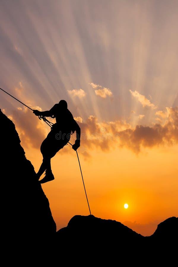 Klättrare på solnedgånghimmelbakgrund royaltyfri fotografi