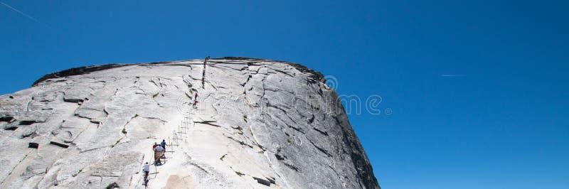Klättrare som använder kablar för att stiga halv kupol i den Yosemite nationalparken i Kalifornien USA royaltyfria bilder