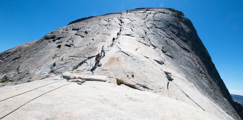 Klättrare som använder kablar för att stiga halv kupol i den Yosemite nationalparken i Kalifornien USA arkivbild