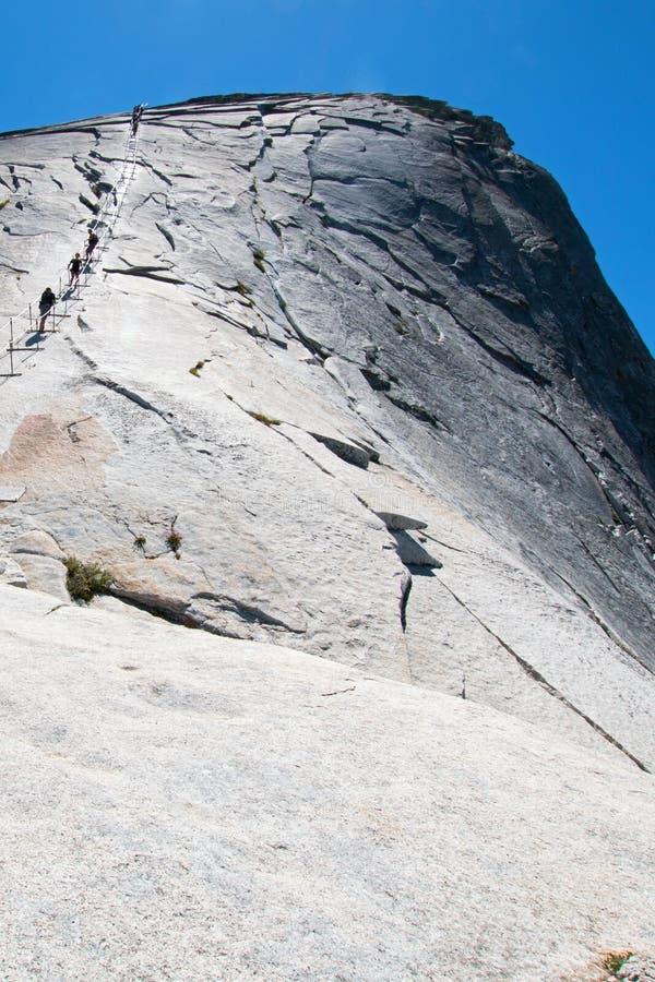 Klättrare som använder kablar för att stiga halv kupol i den Yosemite nationalparken i Kalifornien USA fotografering för bildbyråer