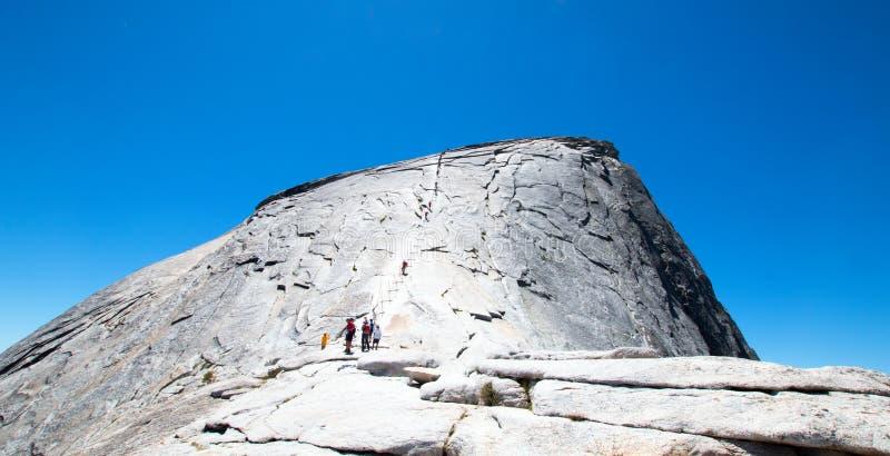 Klättrare som använder kablar för att stiga halv kupol som sett från underkupolen i den Yosemite nationalparken i Kalifornien USA arkivfoton