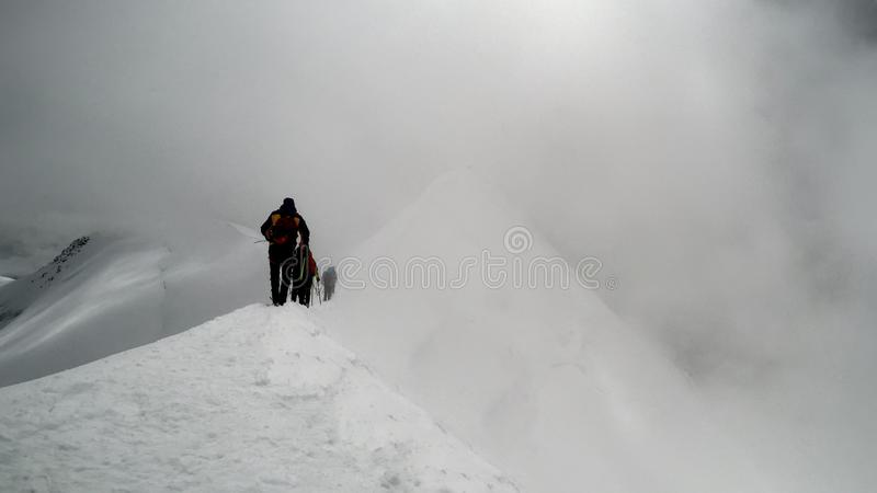 Klättrare som når toppmötet av berget royaltyfri bild