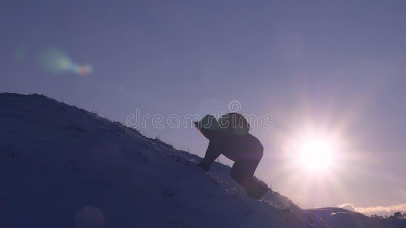 Klättraren klättrar det snöig berget i strålar av den ljusa solen Turisten gör klättring för att överträffa på bakgrund av härlig arkivfoto