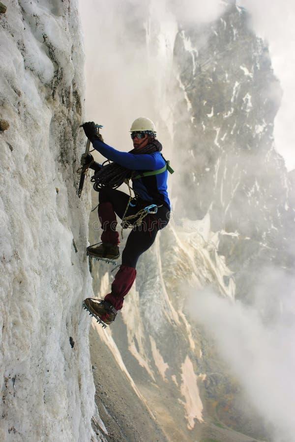 Klättraren med en isyxa klättrar på en vertikal isvägg royaltyfria foton