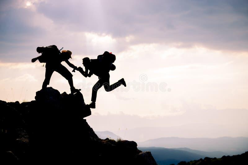 Klättraren når ut till hans partner, genom att hjälpa sig ledande klättrare; Team arbete, livmål och självförbättringsbegreppet arkivfoto