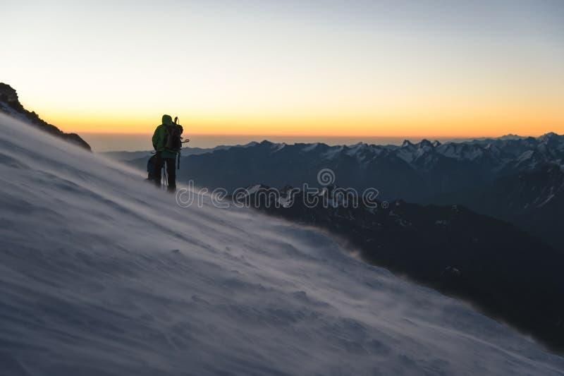 Klättraren på soluppgångottan går på lutningen och på jordningen ovanför snösveparna som driver snö royaltyfri fotografi
