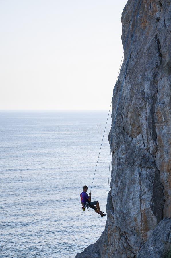 Klättraren stiger ned från berget på solnedgången royaltyfri fotografi