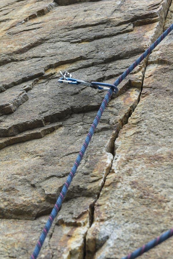 klättring En trådd säkerhetsbult ett rep med en karbin royaltyfri foto