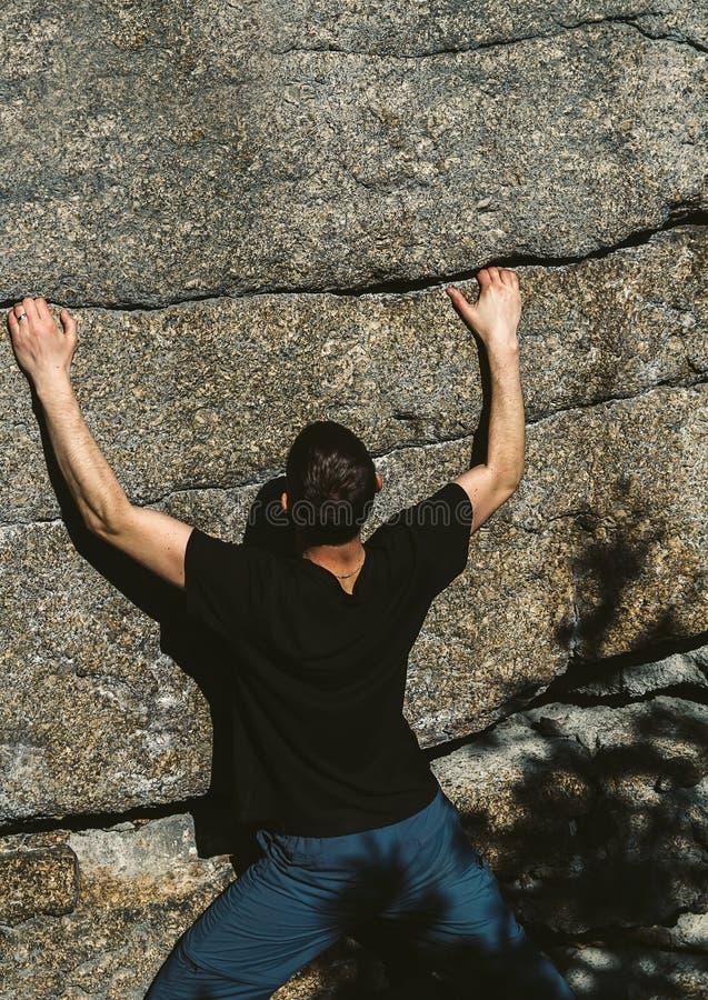 Klättring för den unga mannen vaggar på i liten spricka i sten arkivbild