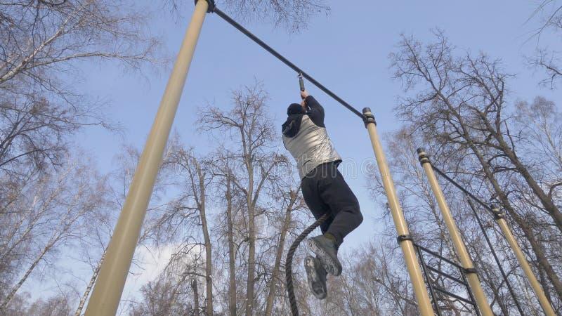 Klättring för stark man på rep under utomhus- genomkörare på sportjordning fotografering för bildbyråer