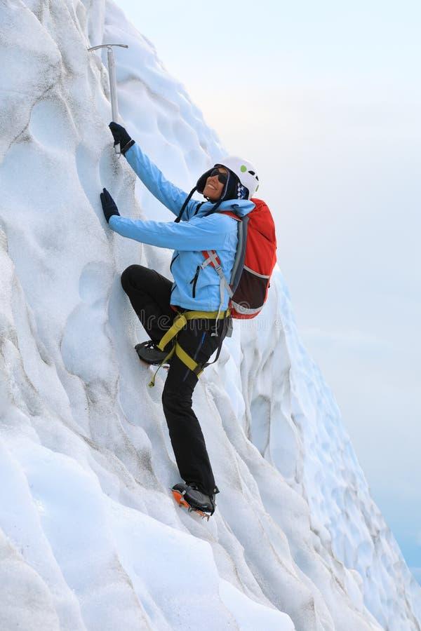 Klättring för ung kvinna på glaciären Falla för Falljokull glaciär arkivbild