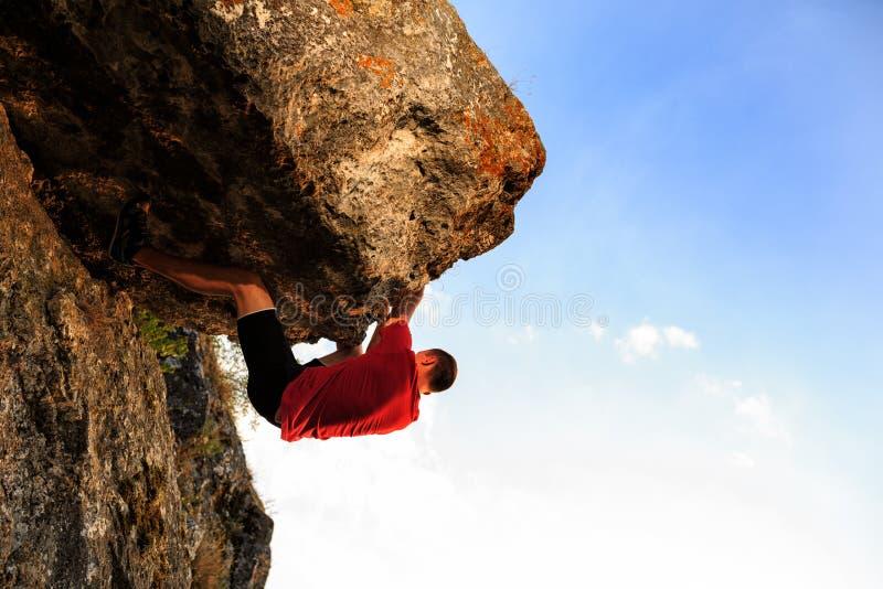Klättring för ung man på en vägg fotografering för bildbyråer