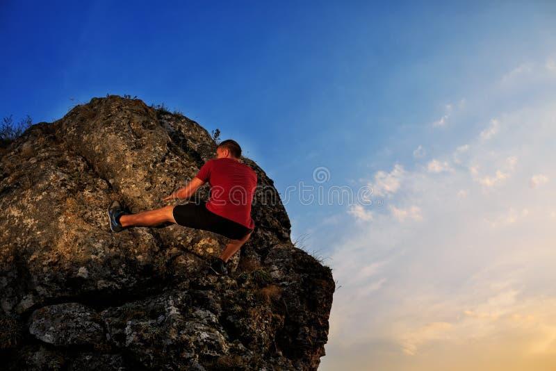 Klättring för ung man på en vägg royaltyfri bild