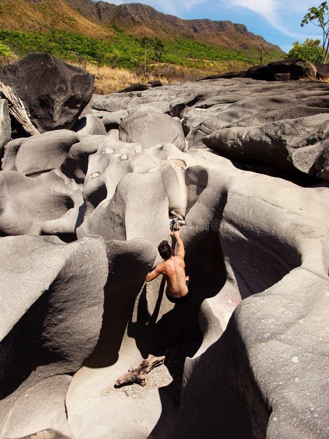 Klättringar för ung man på stenblock vaggar i månedalen, Chapada DOS Veadeiros, Brasilien arkivbild