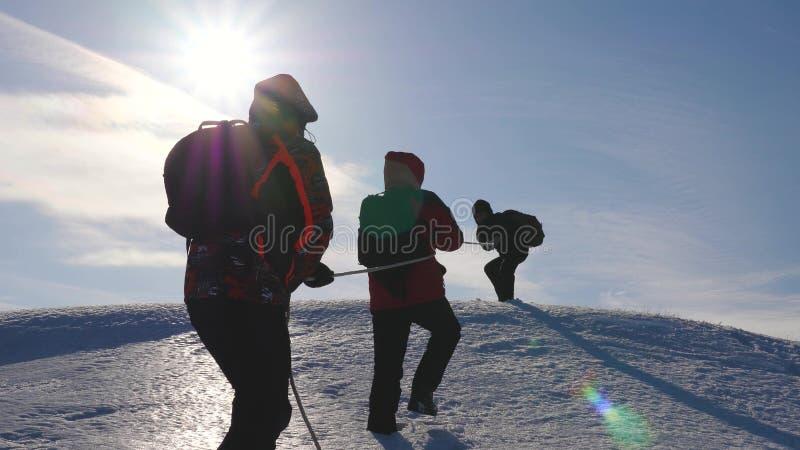 Klättringrep för tre Alpenists på det snöig berget Turister arbetar tillsammans som laget som skakar höjder som övervinner svårig royaltyfri bild
