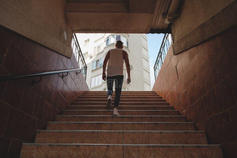 Klättringtrappa för ung man i gångtunnel royaltyfria foton