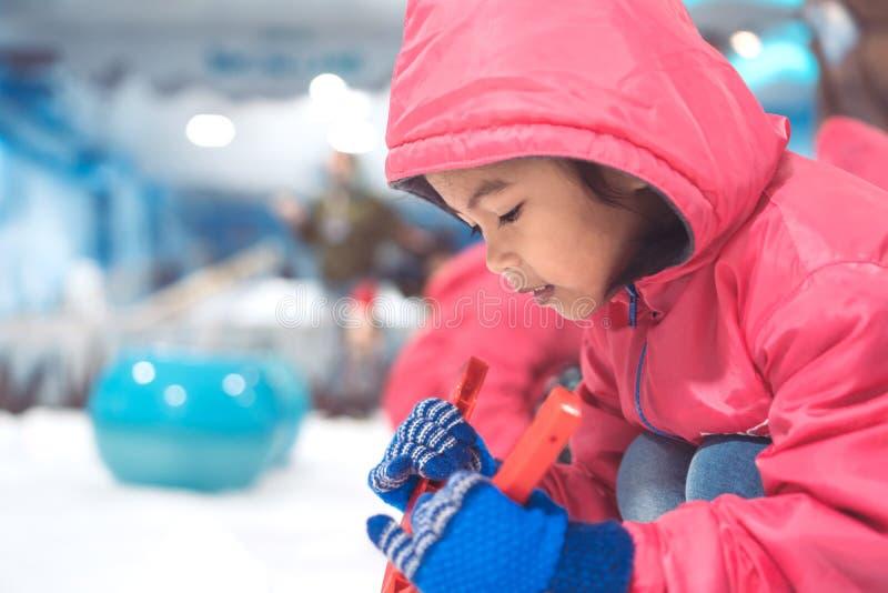 Klår upp bärande rosa färger för gullig asiatisk barnflicka att spela med snö royaltyfria bilder