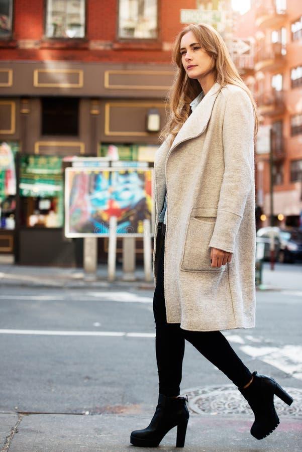 Klår upp den härliga kvinnan för ung adul som går på stadsgatan som bär den tillfälliga dräkten för gatastilhösten med grå färger royaltyfri fotografi