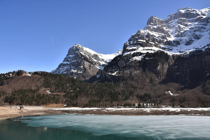 Klöntalersee lake still partly covered with ice and panorama of Alps stock photos