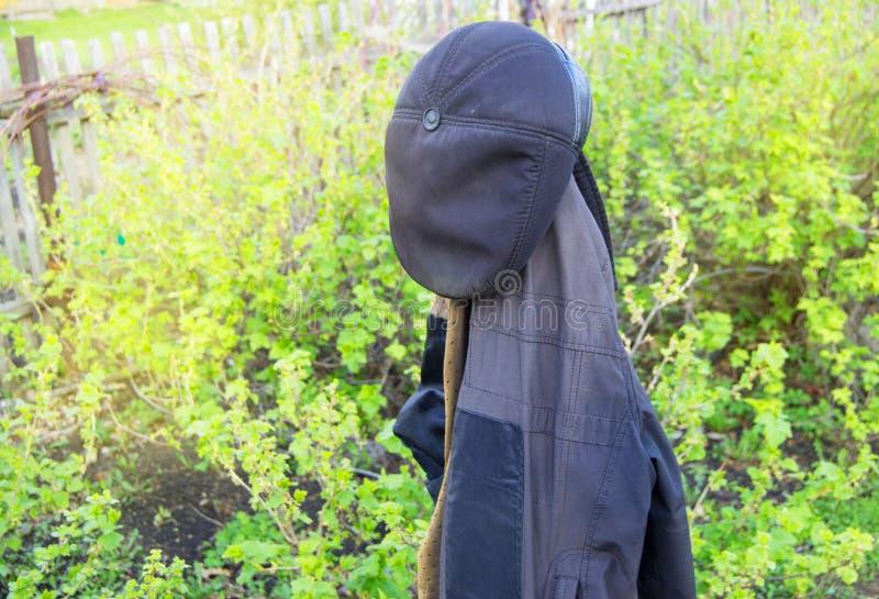 Kl?der f?r arbete f?r man` som s h?nger i det tr?dg?rds- laget och hatten royaltyfri bild