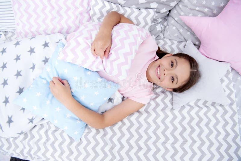 Klaar aan Slaap Het meisje die gelukkig kind glimlachen legt op bed met ster gevormde hoofdkussens en leuke plaid in haar slaapka royalty-vrije stock fotografie