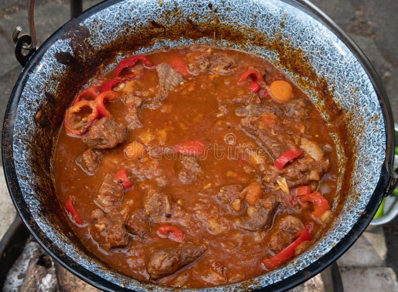 Klaar ketelgoelasj na vier uren kooktijd over een open houten brand Met tomaten, rundvlees, uien, knoflook, knolselder en stock fotografie