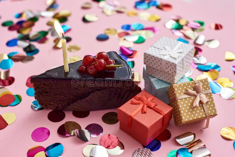 Klaar om de kaarsena plak van chocoladecake met kaars en kleine giftdozen voor uw verjaardag te blazen stock foto's