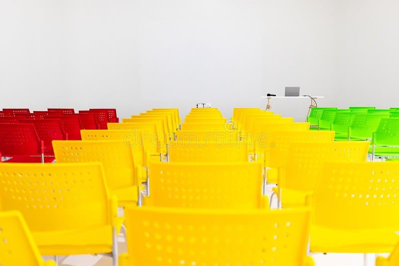 Klaar om rijen van kleurrijke stoelen in conferentieruimte met pro te gebruiken royalty-vrije stock foto
