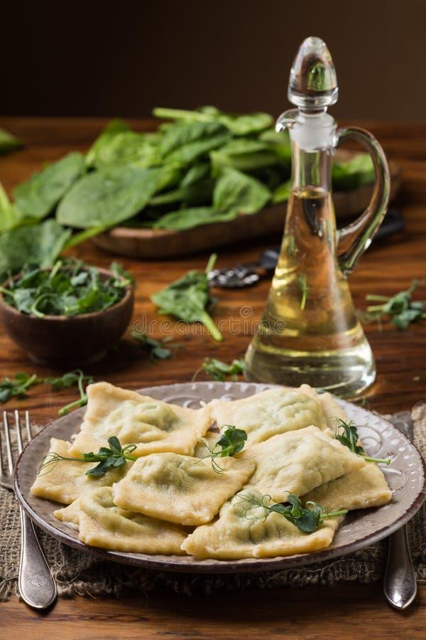 Klaar ravioli in een plaat, spinazie, olijfolie in een kruik royalty-vrije stock foto