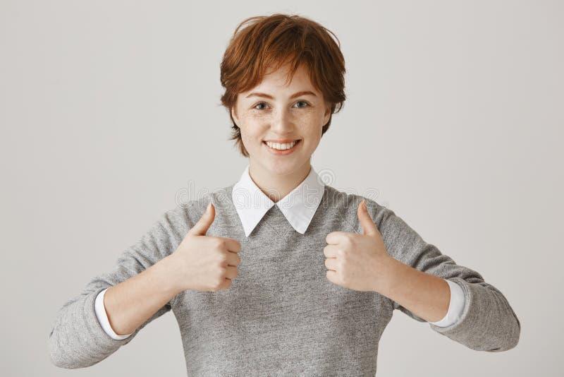 Klaar super vandaag productief te zijn Positieve knappe roodharigevrouw die met sproeten ruim bij camera glimlachen terwijl stock fotografie