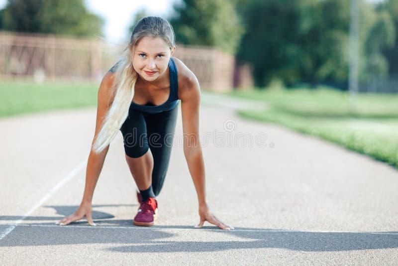 Klaar te gaan! De vrouwelijke atleet in een blauw overhemd en de beenkappen op de beginnende lijn van een stadion volgen het beki stock foto