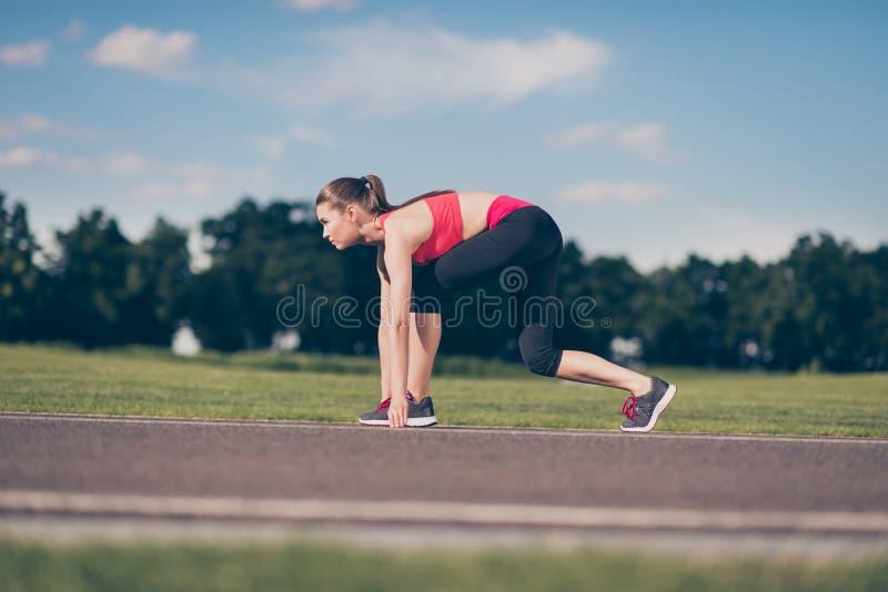 Klaar te gaan! Vrouwelijke atleet op de beginnende lijn van een stadion RT stock fotografie