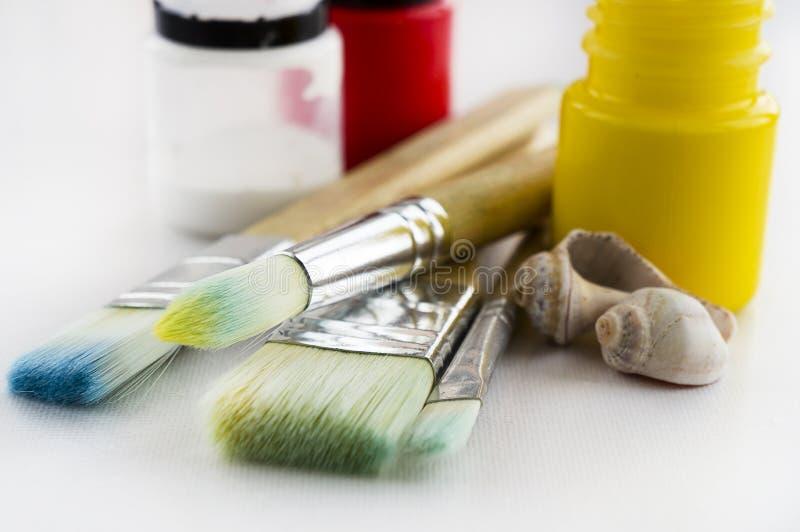 Klackse der Farbe in der Palette mit 2 Bürsten nahe bei Palette Bürsten, Farben seashells lizenzfreie stockfotos