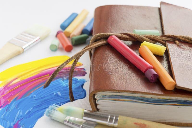 Klackse der Farbe in der Palette mit 2 Bürsten nahe bei Palette Bürsten, Zeichenstifte, Notizbuch lizenzfreie stockfotos
