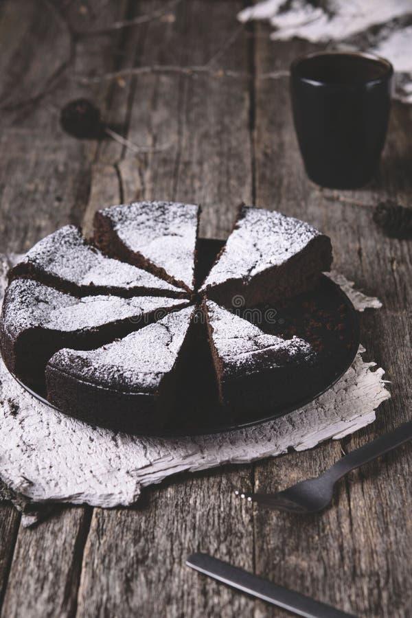 Kladdkaka La torta de chocolate húmeda sueca tradicional en la tabla de madera rústica vieja adornó las ramitas, los conos del pi fotografía de archivo libre de regalías