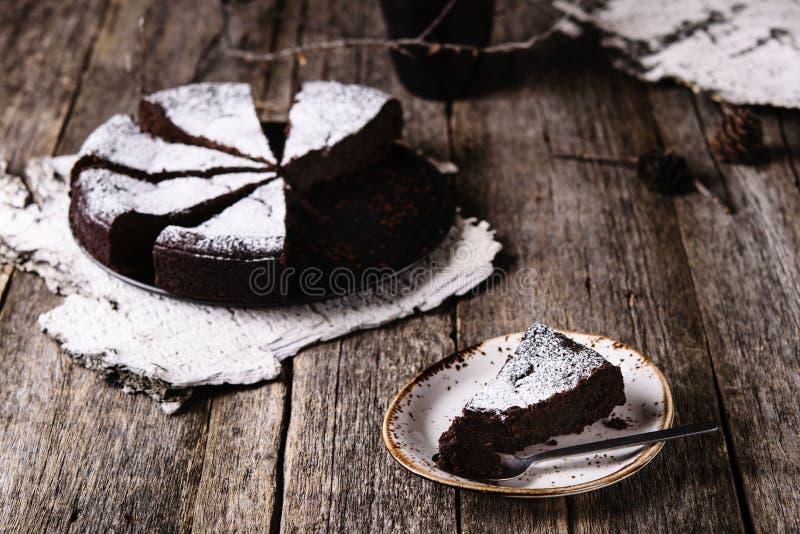 Kladdkaka La torta de chocolate húmeda sueca tradicional en la tabla de madera rústica vieja adornó las ramitas, los conos del pi imágenes de archivo libres de regalías