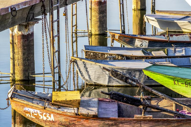 Old boats tied to a pier stock photography