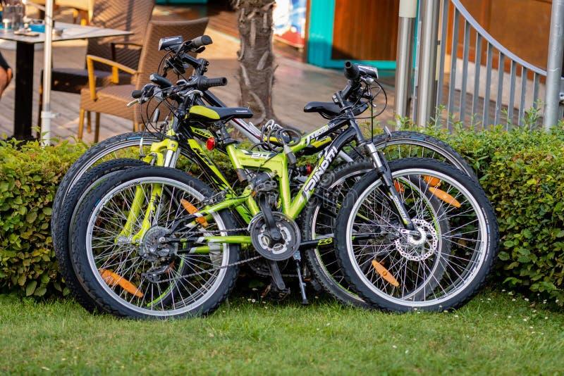 KLAGENFURF, CARINTHIA, AUSTRIA - 7 DE AGOSTO DE 2018: En el parque, al lado de la cafetería, tres bicicletas parqueadas fotos de archivo