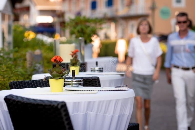 KLAGENFURF, CARINTHIA AUSTRIA, SIERPIEŃ, - 07, 2018: Kawiarnia stoły na ulicie W tle jest ulica z ludzkimi sylwetkami zdjęcie stock