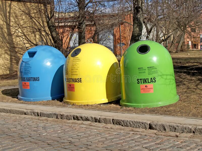 KLAIPEDA, LITHUANIA. Colored containers for separate collection of garbage. Lithuanian text - glass, plastic, paper. KLAIPEDA, LITHUANIA - MARCH 14, 2012 royalty free stock images