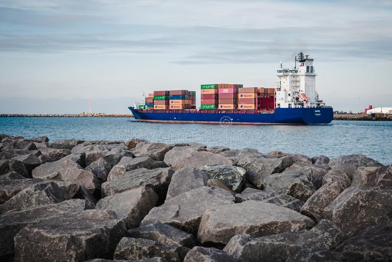 KLAIPEDA, LITHUANIA - November 24, 2019: Sea gate of Klaipeda harbour. The containership leaving the harbour to the sea royalty free stock photo