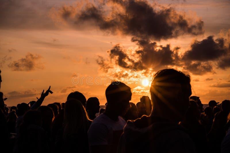 KLAIPEDA, LITOUWEN - AUGUSTUS 19, 2017: Zonsonderganglicht met Mensen en Schaduwen Zonsondergang bij Oostzeestrand stock afbeelding
