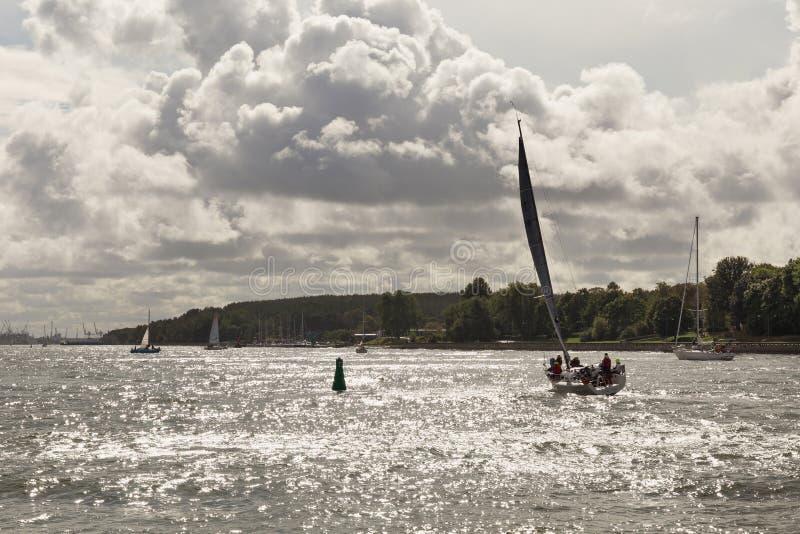 KLAIPEDA, LITUÂNIA - 22 DE SETEMBRO DE 2018: Os iate pequenos estão navegando nas águas da lagoa de Curonian perto do porto de Kl imagens de stock royalty free